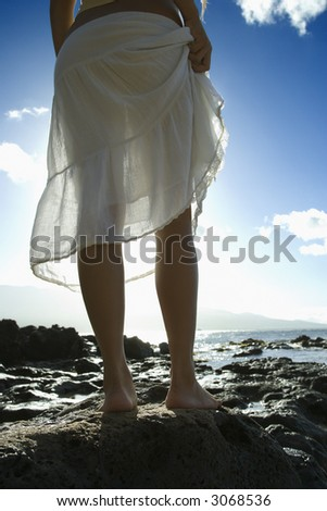 Legs of young adult Asian Filipino female standing on rocky beach in Maui Hawaii. - stock photo
