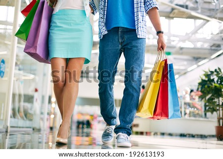 Legs of young couple going in the mall - stock photo