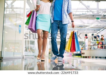 Legs of young couple shopping in trade center - stock photo