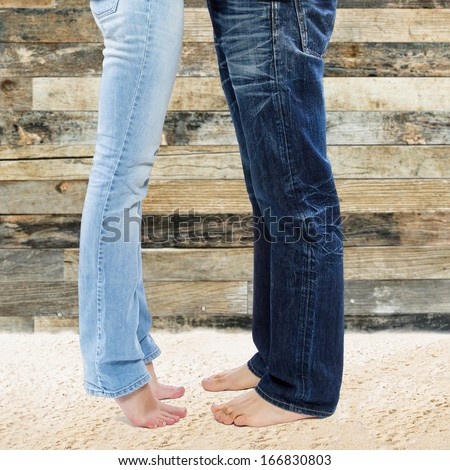 Legs of young couple standing on the sand against vintage wooden background  - stock photo