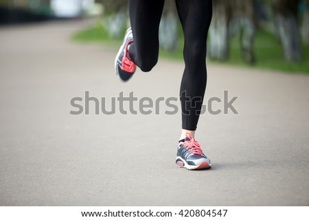 Legs of young female model running in park during everyday practice. Fitness woman in training shoes jogging outdoors in park. Sport active lifestyle concept. Close-up view - stock photo