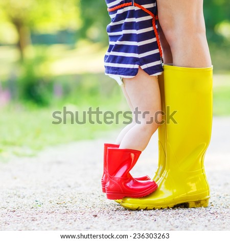 Legs of young woman and her little girl daugher in rainboots. - stock photo