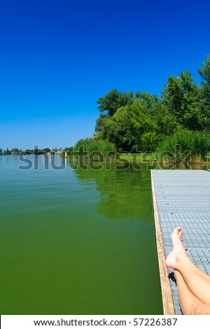 legs over the green lake in Tata - stock photo