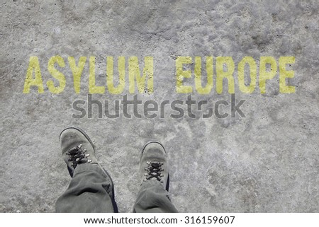legs with gray boots and the words Asylum and Europe on the ground. Concept for Refugees on their way to Europe. - stock photo