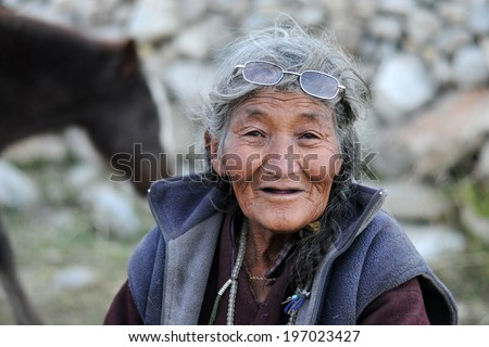 LEH IN LADAKH, INDIA - SEPTEMBER 17 2012: Old unidentified local woman sitting outdoor in Leh. The majority of the local population are descendant of Tibetan. - stock photo