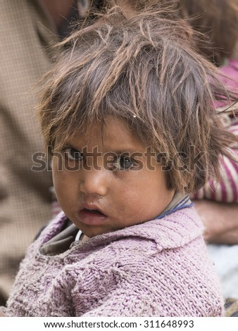 LEH, INDIA - JUNE 29, 2015: Unidentified poor Indian beggar girl on street in Ladakh. Children of the early ages are often brought to the begging profession. - stock photo