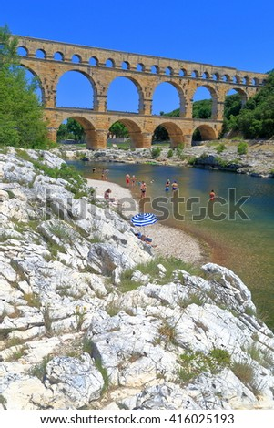 Leisure activities on the river banks under Pont du Gard - an ancient aqueduct across the River Gardon near Nimes, France - stock photo