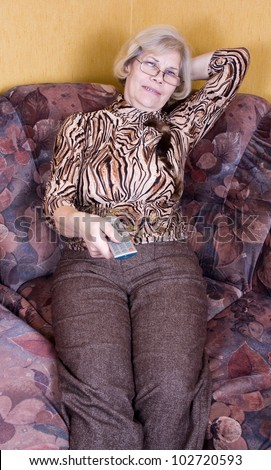 Leisure activity - Elderly woman relaxing on couch and watching television - stock photo