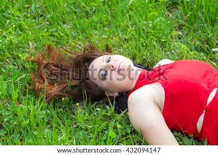 leisure and people concept - young girl in red lying on grass - stock photo