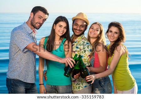 Leisure at sea. Weekend abroad. Youth party at sea. Funny guys and girls resting on vacation. Young people drink beverages on the beach. - stock photo