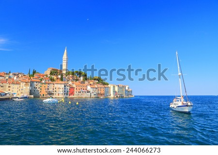 Leisure boats and distant Venetian town surrounded by the Adriatic sea, Rovinj, Croatia - stock photo