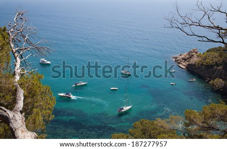 Leisure boats lazily anchored off an idyllic coast. View from above - stock photo