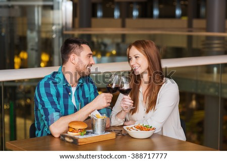 leisure, celebration, food and drinks, people and holidays concept - smiling couple having dinner and drinking red wine at date in restaurant - stock photo