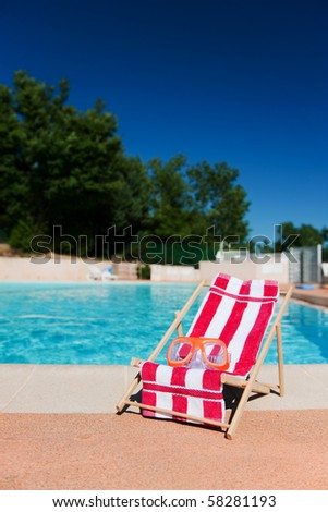 leisure chair with goggles at the swimming pool - stock photo