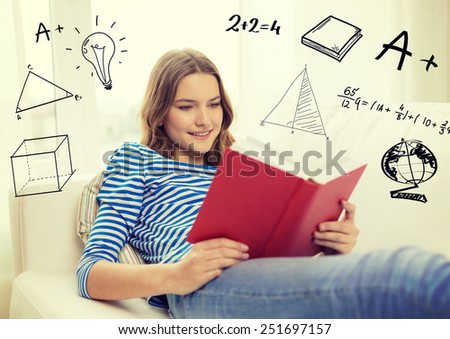 leisure, education and home concept - smiling teenage girl in glasses reading book and sitting on couch at home - stock photo