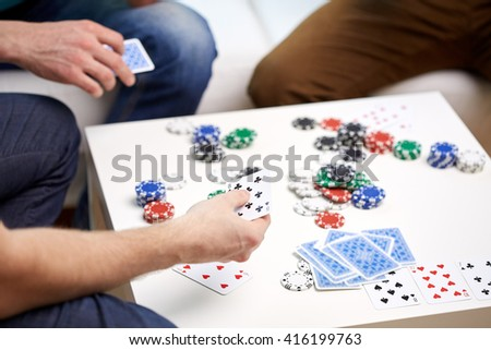 leisure, games, friendship, gambling and entertainment - close up of male friends playing cards at home - stock photo