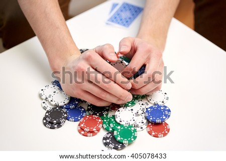 leisure, games, gambling and entertainment - close up of male hands with casino chips and playing cards making bet or taking win at home - stock photo