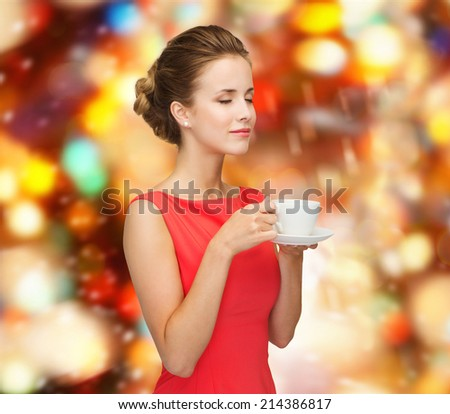 leisure, happiness, holidays and drink concept - smiling woman in red dress with closed eyes holding cup of coffee over shiny lights background - stock photo