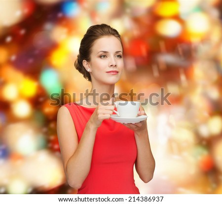 leisure, happiness, holidays and drink concept - smiling woman in red dress with cup of coffee over shiny lights background - stock photo