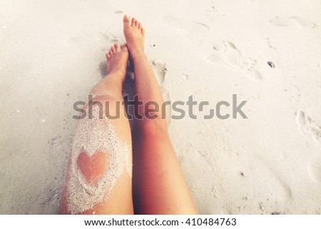 Leisure in summer - Beautiful women tan. relax on beach with sand of heart shape. retro filter effect - stock photo