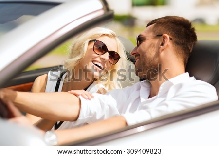 leisure, road trip, dating, couple and people concept - happy man and woman driving in cabriolet car outdoors - stock photo
