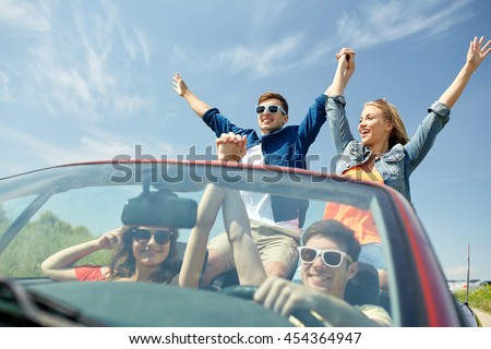 leisure, road trip, travel and people concept - happy friends driving in cabriolet car at country and waving hands - stock photo