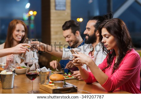 leisure, technology, internet addiction, lifestyle and people concept - woman with smartphone and friends at restaurant - stock photo