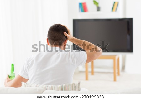 leisure, technology, mass media and people concept - man watching tv, drinking bottle beer and suffering from headache at home from back - stock photo