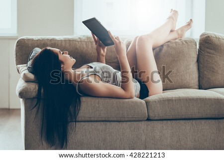 Leisure time at home. Beautiful young woman in panties and tank top holding digital tablet and looking at it with smile while lying on couch at home - stock photo
