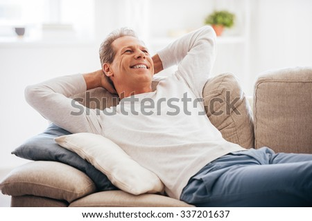 Leisure time at home. Cheerful mature man holding hands behind head while lying on the couch at home - stock photo
