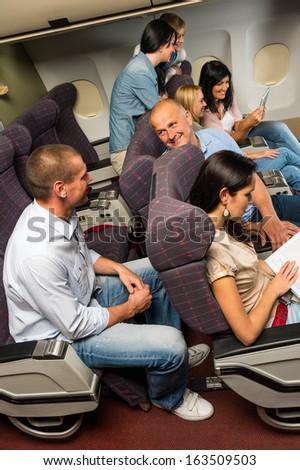 Leisure travel people enjoy flight airplane cabin talking passengers - stock photo