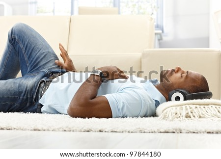 Leisure with music, ethnic man lying on living room floor with headset, enjoying with closed eyes. - stock photo