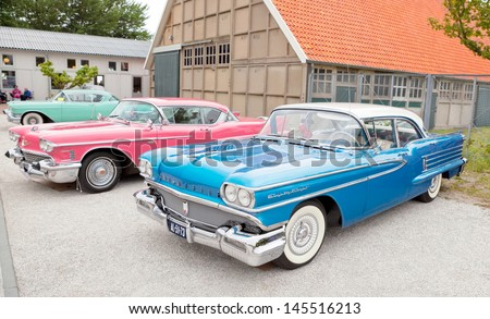 LELYSTAD - JUNE 16: Blue 1958 Oldsmobile Eighty Eight, pink 1958 Cadillac Coupe de Ville, and other cars are on display at the annual National Oldtimer day, June 16, 2013 in Lelystad, The Netherlands - stock photo
