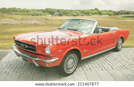 LELYSTAD, THE NETHERLANDS - JUNE 17 2012: 1965 Ford Mustang Convertible on display during annual National Oldtimer day. Textured photograph in a retro-like look. - stock photo