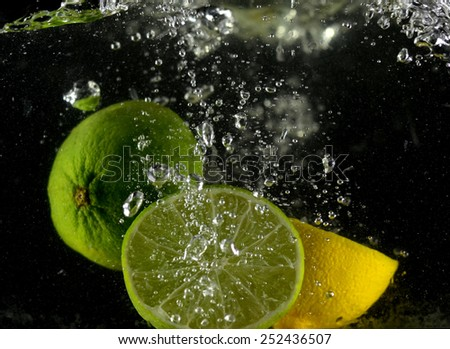 lemon and lime in water drop (on the black background) - stock photo