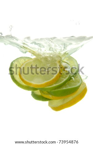 Lemon and lime thrown into the water with splash, on white background. - stock photo