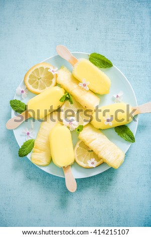Lemon and pineapple popsicles with fresh fruits and edible flowers - stock photo