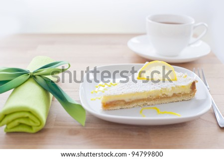 lemon cake on a white porcelain plate, dessert fork and a napkin tied with a bow green in the background with a cup of tea, wooden table - stock photo
