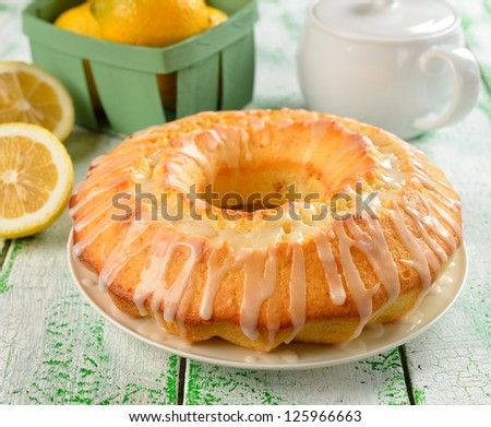 Lemon cake with frosting on a green table - stock photo
