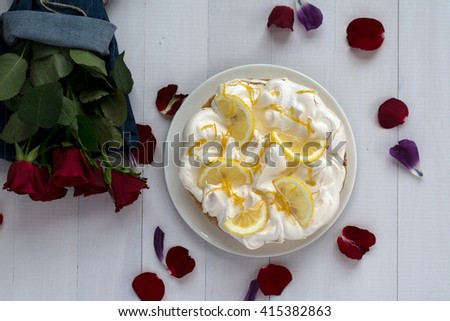 Lemon cake with roses top view. Lemon tart with meringue and lemon slices. Table top view. White wood background. Roses petals. Red roses bouquet wrapped in jeans material. - stock photo