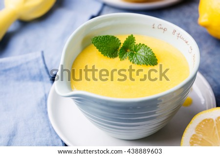 Lemon curd in ceramic bowl with fresh lemons on a blue napkin background. Selective focus  - stock photo