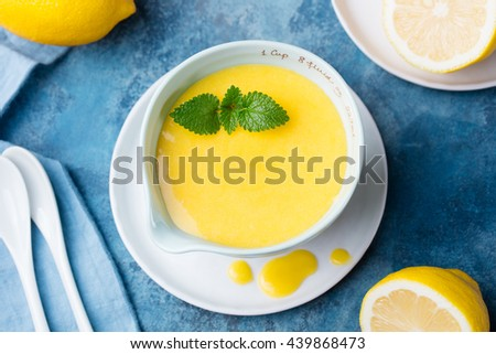 Lemon curd in ceramic bowl with fresh lemons on a blue napkin background. Top view. Selective focus - stock photo