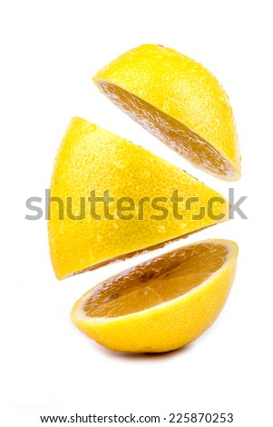 Lemon cut into pieces and parts flying in the air - stock photo