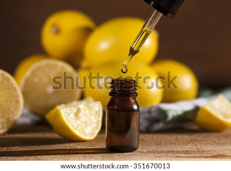 Lemon essential oil and lemon fruits on wooden background - stock photo