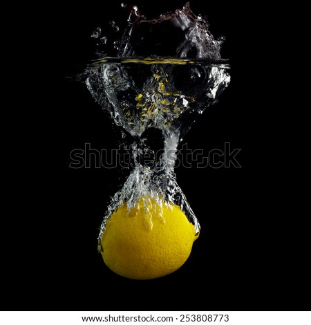 Lemon falling into the water with a splash of water and air bubbles. On a black background. Wash fruits. - stock photo