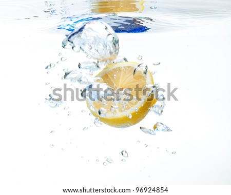 Lemon floating in the water on a white background - stock photo