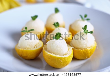 Lemon icecream served in half of lemon in white plate on white background. - stock photo