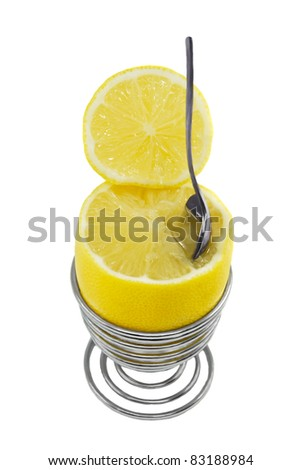 Lemon in the metal spiral eggcup with spoon on the white background - stock photo