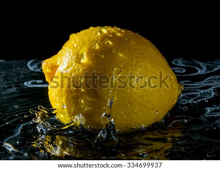 Lemon in water with reflection from water splashes on black background - stock photo