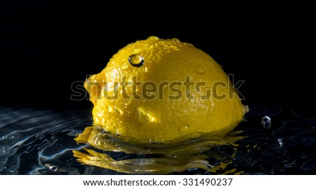 Lemon in water with reflection from water splashes with drops on black background  - stock photo